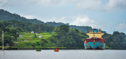 A large cargo ship makes its way through the Panama Canal, lined with green jungle on both sides.
