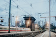 Zug fährt bei Dämmerungen durch den Bahnhof einer Großstadt