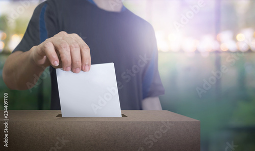 Fotografie, Obraz  Hand holding ballot paper for election vote at place election background