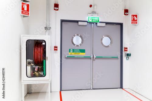 Obraz na plátně Exit sign and fire extinguisher at building.
