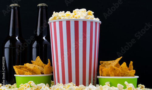 a bucket of popcorn, two buckets of nachos and a bottle of beer, on a black background