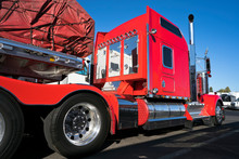 Bright Red Big Rig Classic American Semi Truck With Flat Bed Semi Trailer Carry Commercial Cargo Covered And Fixed By Slings Stand On Truck Stop
