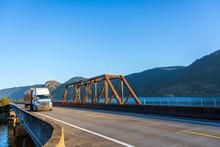 White Big Rig Semi Truck Transporting Cargo In Orange Semi Trailer Driving On The Bridge Across The Columbia River