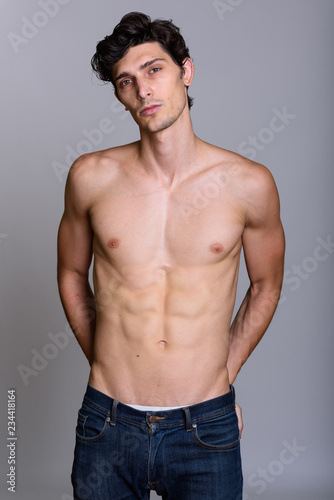 1ba74a999ad05 Studio shot of young handsome man shirtless with hands on back p ...