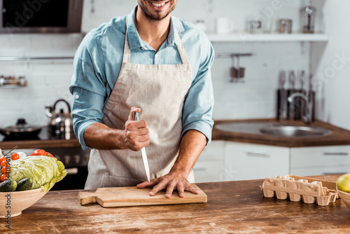 Fotografie, Obraz  cropped shot of smiling young man in apron holding knife and hand on chopping bo