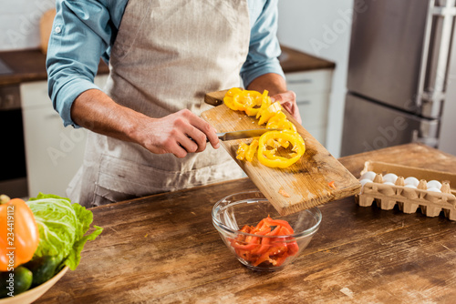 Fototapety, obrazy: mid section of man in apron cooking vegetable salad in kitchen