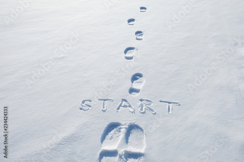 Photo Concept picture.inscription start and footprints in the snow