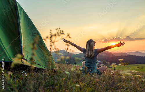 Happy woman with open arms stay near tent around mountains under sun