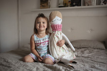 Toddler Girl With Soft Handmade Doll In Bedroom