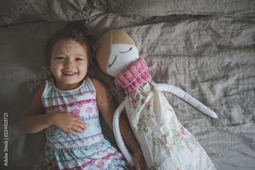 Canvas Print Toddler girl with soft handmade doll in bedroom