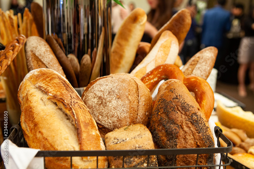 Assortment of freshly baked breads in a wire basket for appetizer or meal starter. Looks tasty and delicious. Good source of carbohydrate. Not gluten-free. Staple food of people. Selective Focus.