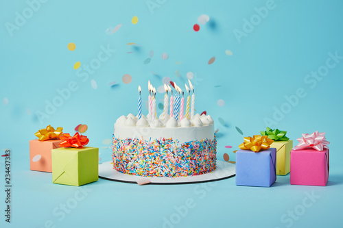 Photo  Tasty cake with candles, colorful gifts and confetti on blue background