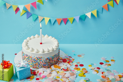 Delicious cake with sugar sprinkles, gifts and confetti on blue background with colorful bunting