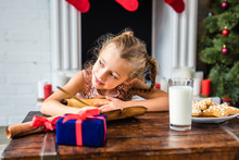 Cute Smiling Child Looking Away While Writing Wishlist At Christmas Time