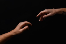 Male And Female Hands Reaching Out To Each Other On Dark Background