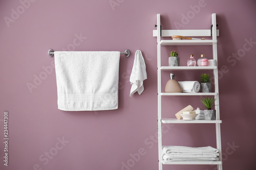 Valokuva  White clean towels and shelves with cosmetics on color background