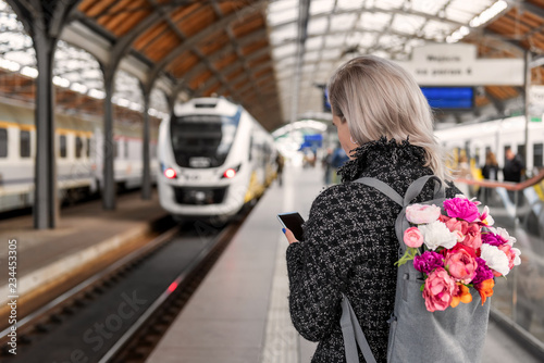 Fotografía  Blonde woman with backpack with bouquet of flowers is holding smartphone and waiting train