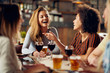 canvas print picture - Multicultural friends sitting in restaurant and drinking wine and beer.