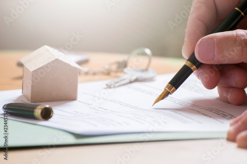 Fototapeta Man hand signing documentation for home mortgage with a pen. Keys and home icon with empty copy space for Editor's text. obraz