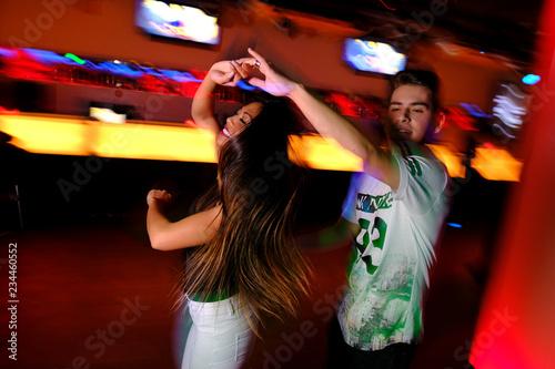 Pareja joven bailando salsa y bachata en una fiesta en club nocturno Canvas-taulu