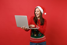 Laughing Young Santa Girl In Knitted Sweater, Christmas Hat Working, Typing On Laptop Pc Computer Isolated On Red Background. Happy New Year 2019 Celebration Holiday Party Concept. Mock Up Copy Space.