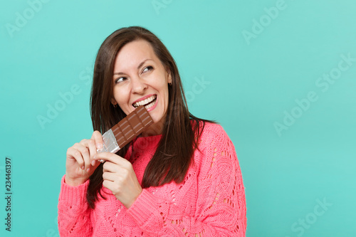 Fotografie, Tablou  Pretty young woman in knitted pink sweater holding in hand biting chocolate bar looking aside isolated on blue turquoise wall background, studio portrait