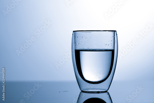 Fotografía  glass of purity water with water drops  on blue background