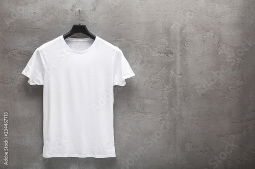 Fotografía Front side of male white cotton t-shirt on a hanger and a concrete wall in the background
