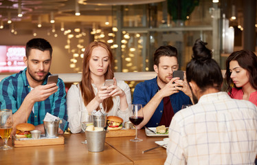 Fototapeta leisure, technology, lifestyle and people concept - friends with smartphones dining at restaurant