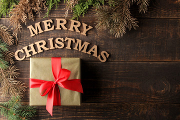 text merry christmas. gold letters and gift and christmas tree branches on brown wooden background. Top view with space for inscription. new Year. Christmas. holidays