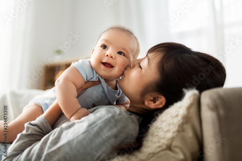 Foto  family and motherhood concept - happy young asian mother kissing little baby son