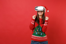 Pretty Young Santa Girl In Knitted Sweater, Christmas Hat Looking In Headset Clenching Fists Isolated On Red Wall Background. Happy New Year 2019 Celebration Holiday Party Concept. Mock Up Copy Space.