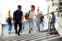Motion Blur Shot Of High School Students Walking On Stairs Between Lessons In Busy College Building