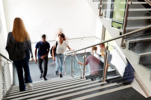 Obraz na płótnie Motion Blur Shot Of High School Students Walking On Stairs Between Lessons In Bu