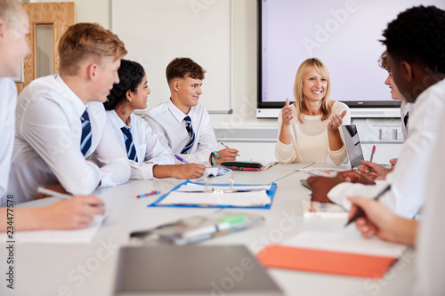 Female High School Teacher Sitting At Table With Teenage Pupils Wearing Uniform Fototapeta