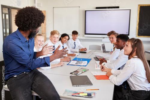 Fototapeta Male High School Teacher Sitting At Table With Teenage Pupils Wearing Uniform Teaching Lesson obraz na płótnie