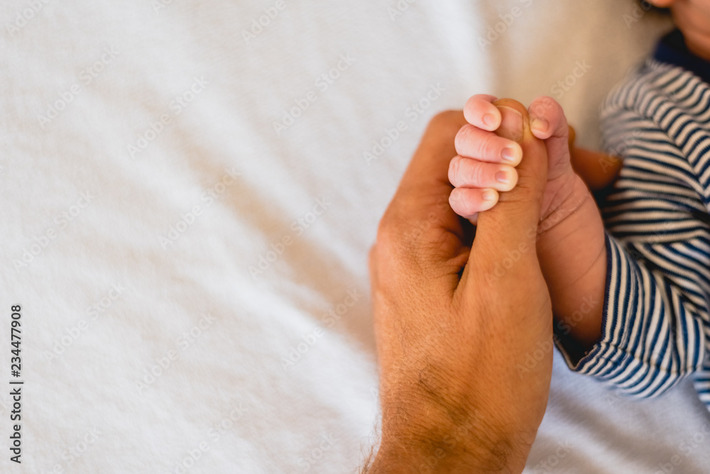 Fototapety, obrazy: Newborn baby securely grasping his mother's hands, close-up fingers.