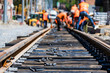 canvas print picture - Workers in bright uniforms lay railway or tram tracks