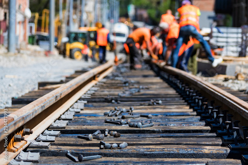 Fotografie, Obraz Workers in bright uniforms lay railway or tram tracks