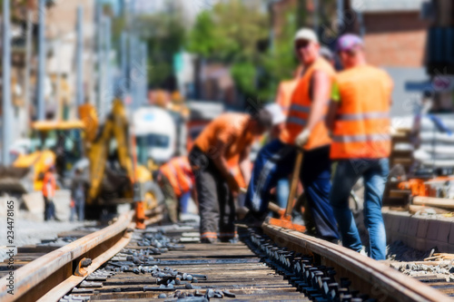 Obraz na plátně Workers in bright uniforms lay railway or tram tracks