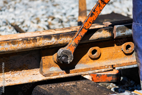 Fotomural  Worker tightens the skrew in railway or tram tracks
