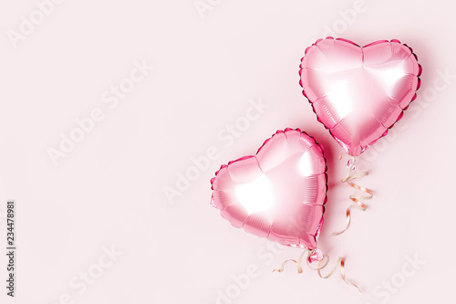 Air Balloons of heart shaped foil  on pastel pink background. Love concept. Holiday celebration. Valentine's Day or wedding/bachelorette party decoration. Metallic balloon