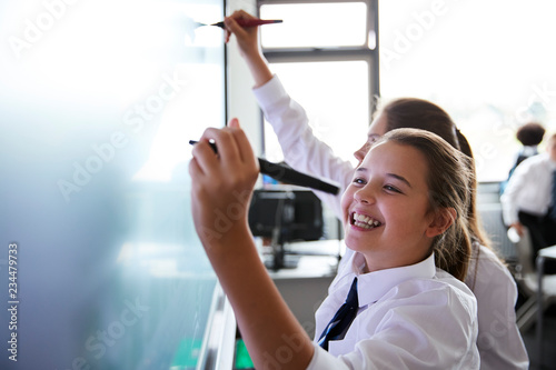 Foto Female High School Students Wearing Uniform Using Interactive Whiteboard During