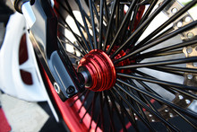 Chopper Motorcycle Wheel Closeup With A Pattern Of Shiny Black Spokes.