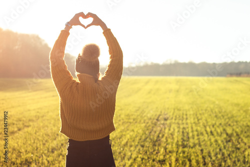 Tuinposter Zwavel geel Junge Frau formt mit beiden Händen ein Herz