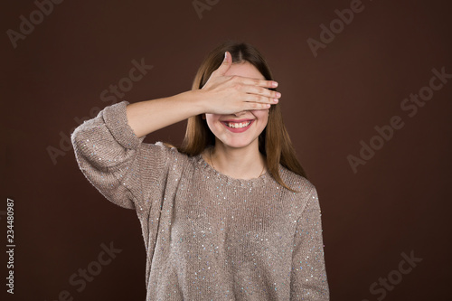 Obraz na plátně smiley woman covering her eyes by hands over brown background