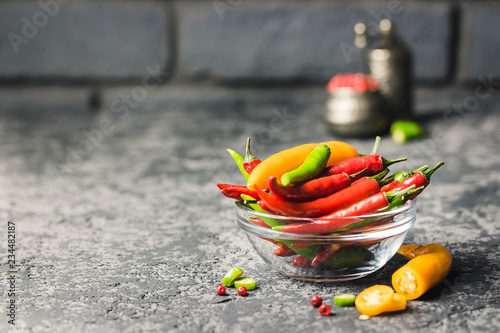 фотография Red, yellow, green chili peppers in a bowl on dark concrete background