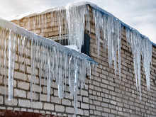 Dangerous Huge And Long Icicles On The Roof Of The Building. Construction Defects Causing Damages In Winter. Winter Season Background