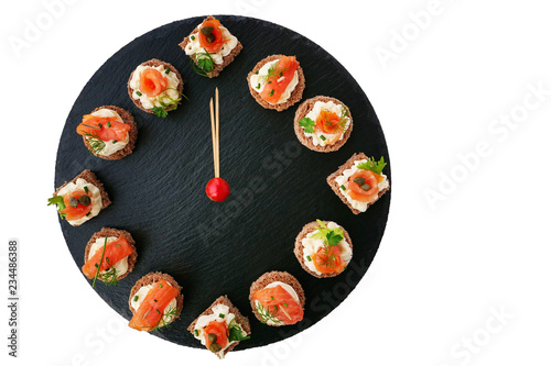 Foto op Aluminium Assortiment Happy New Year! Smoked salmon canapes on black slate platter form a clock face showing midnight.