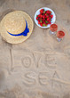 straw hat, wine and a plate of strawberries on a sandy beach-inscription love the sea.